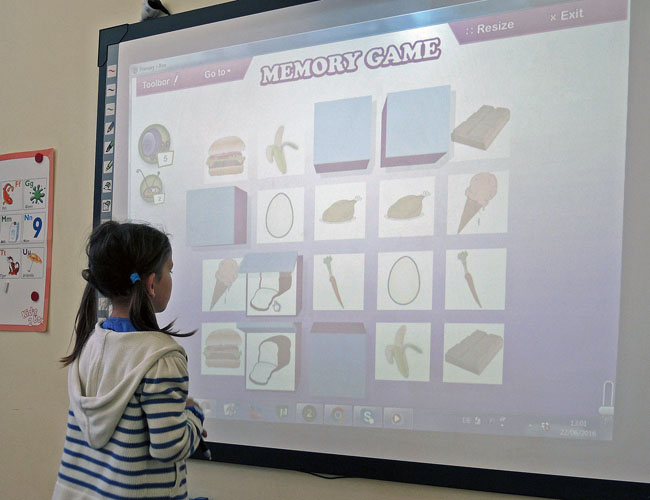 A girl standing in front of the white board